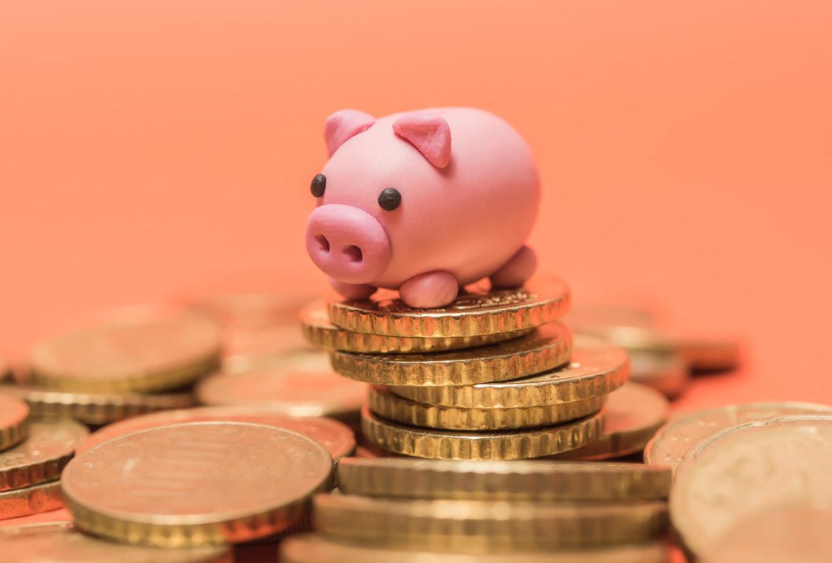 figura de un cochinito sobre una pila de monedas