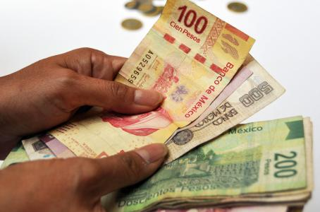 muchos billetes sostenidos con ambas manos