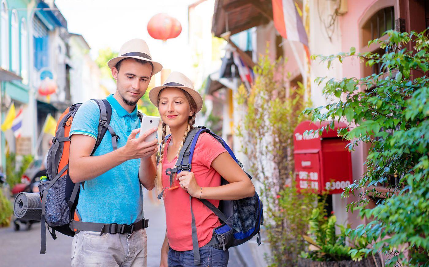 Una pareja viendo su smarthpone en medio de una calle