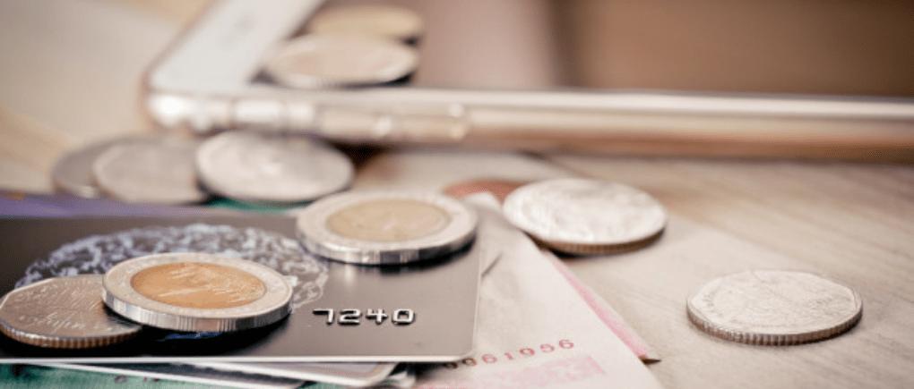 Monedas, tarjetas de crédito y un celular